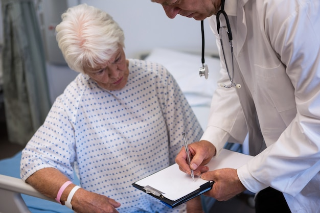 Doctor discussing medical report with senior patient