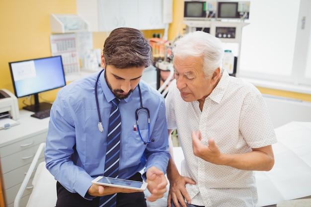 Доктор обсуждает с пациентом над цифровым планшетом