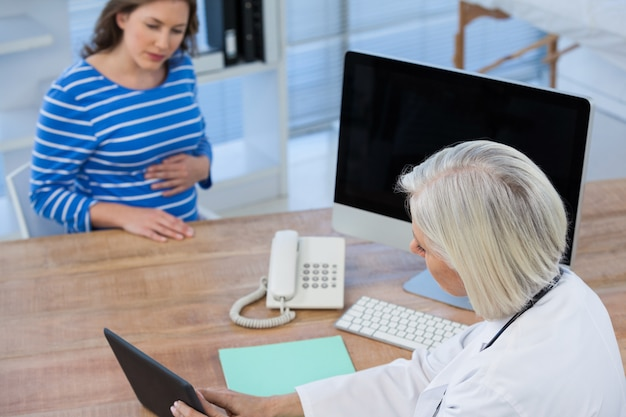 Doctor discussing with pregnant patient over digital tablet