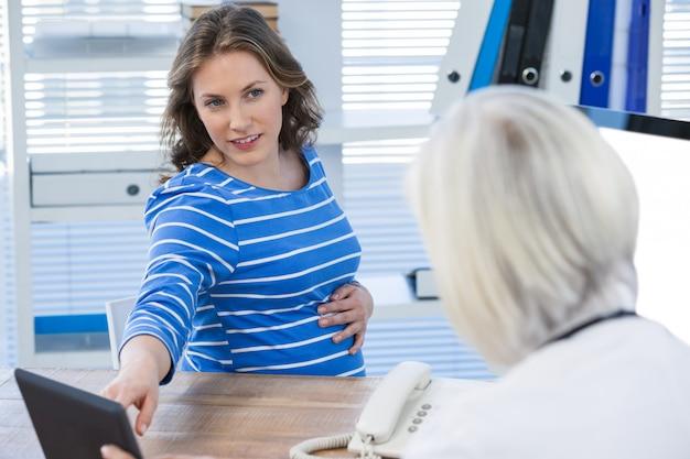 Доктор обсуждает с беременной пациенткой на цифровой планшет