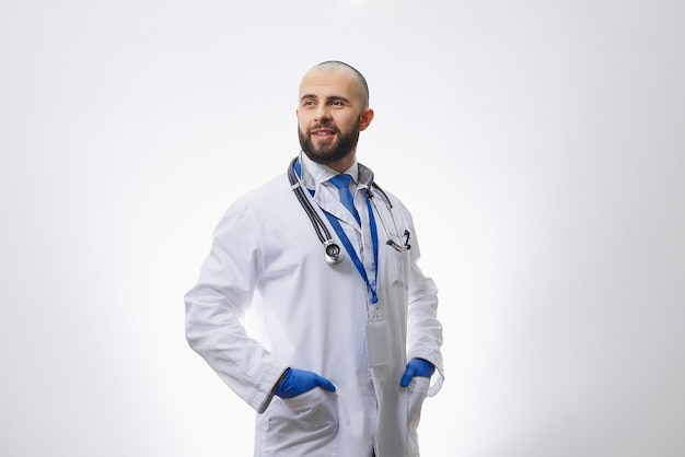 A doctor in disposable medical gloves with a stethoscope holding hands in pockets.