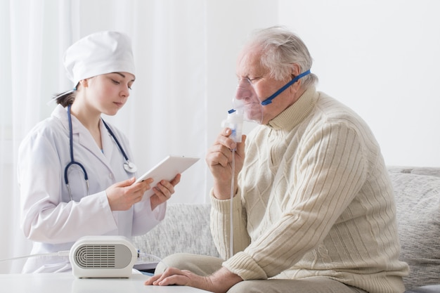 Doctor does inhalation elderly man