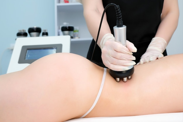 Doctor does the rf lifting procedure on the legs, buttocks and back, hips of a woman in a beauty parlor. treatment of overweight and flabby skin.