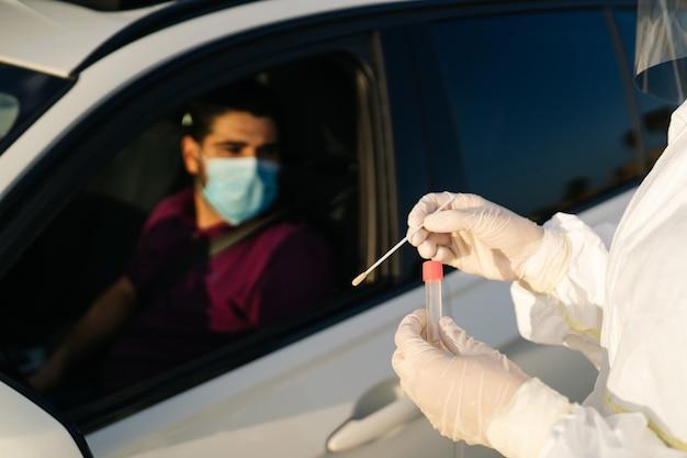 Врач проводит пцр-тест на covid-19 на пациенте через окно автомобиля.