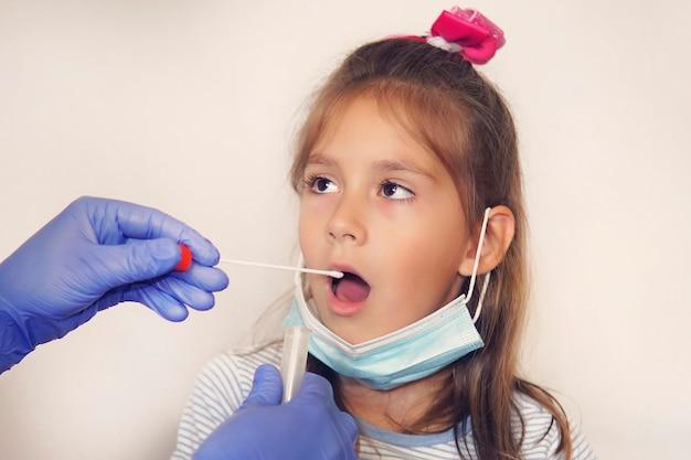 少女患者のためにコロナウイルス検査を行う医師。 dna検査。実験室での研究のための喉からの粘液の収集。男性から唾液サンプルを採取します。