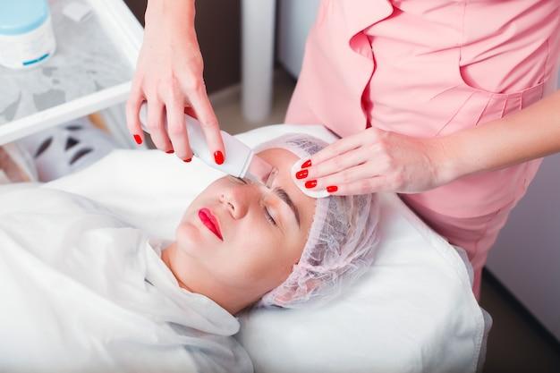 Врач делает медицинскую процедуру с ультразвуковым скребком. ультразвуковая чистка лица. косметология. здравоохранение.