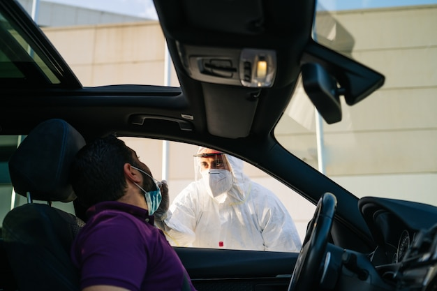 Doctor doing a pcr test covid-19 on a patient through the car window.