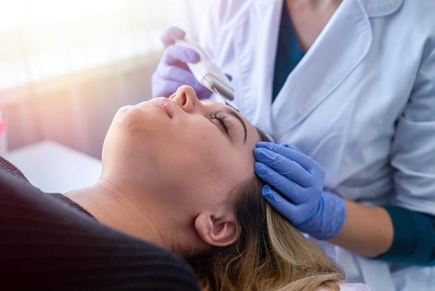 미용실에서 얼굴 환자의 초음파 세척 절차를 수행하는 의사