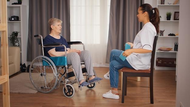 車いすで年配の女性とリハビリをしている医者。トレーニング、スポーツ、回復とリフティング、老人ホーム、ヘルスケア看護、健康サポート、社会的支援、医師と在宅サービス