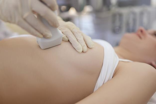 클리닉 근접 촬영에서 젊은 여성에게 유방의 초음파 검사를하는 의사