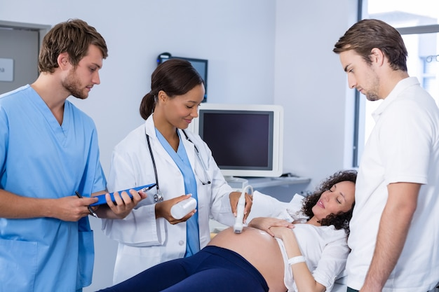 Doctor doing ultrasound scan for pregnant woman