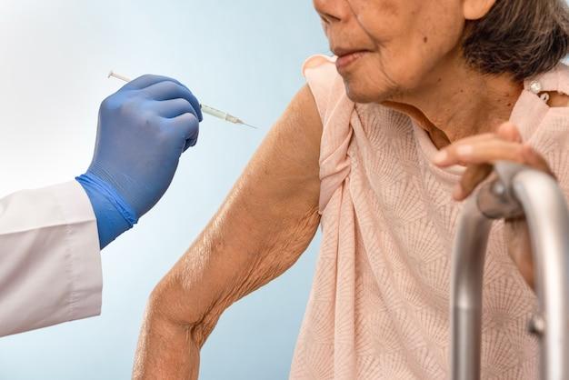 年配の女性にワクチン注射をしている医者。
