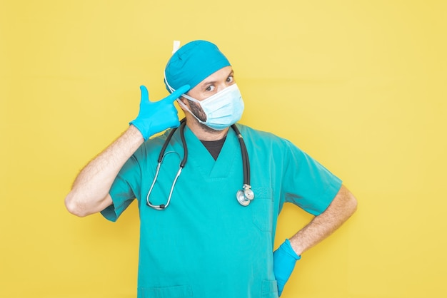의사는 걱정 식 노란색 배경에 청진 기 및 마스크와 녹색에서 외과 의사로 옷을 입고.