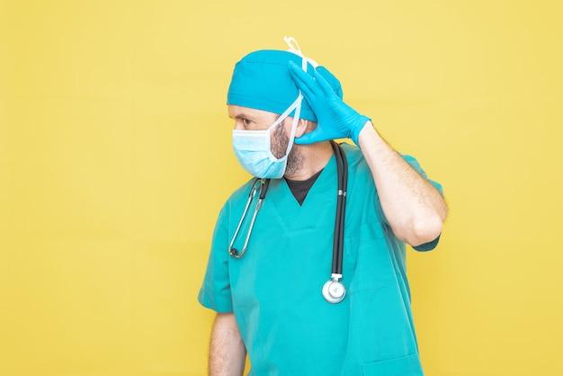 心配そうな表情で黄色の背景に聴診器とマスクを備えた緑色の外科医に扮した医師。