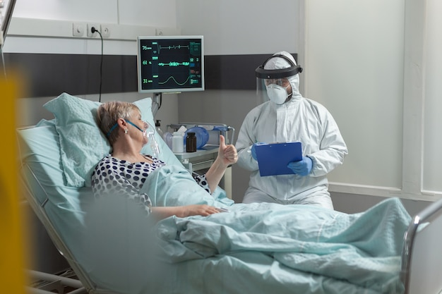 Доктор, одетый в костюм ppe с лицом shiled, обсуждает со старшим пациентом