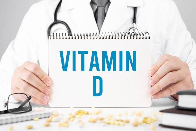 Doctor in a dressing gown holds a notepad with text vitamin d, medical concept