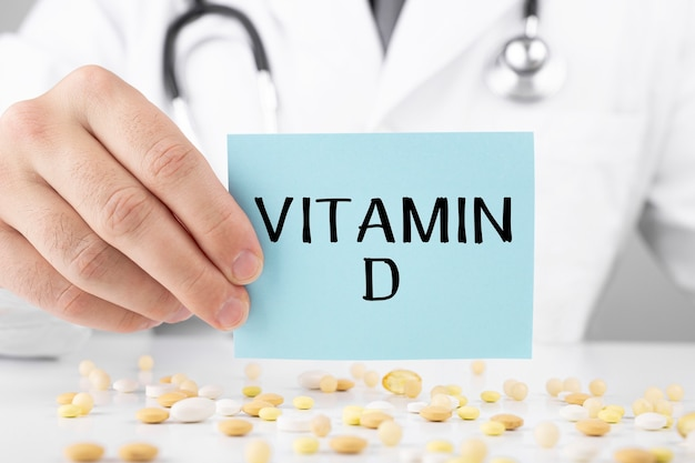 Doctor in a dressing gown holds a sticker with text vitamin d