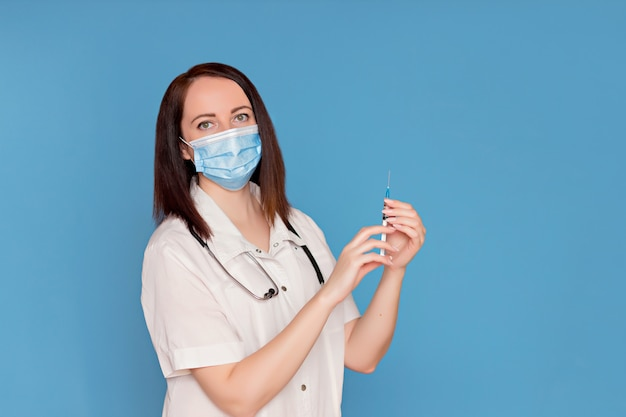 Doctor in a dressing gown with a stethoscope in a medical mask holds an injection syringe