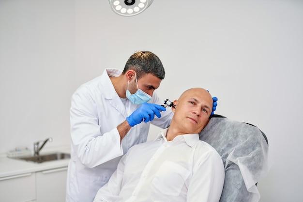 Врач лор проверяет ухо с помощью отоскопа пациенту в больнице