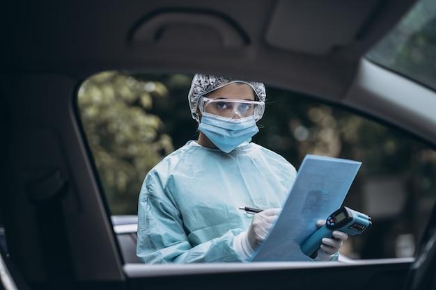 Врач эпидемиолог борется с коронавирусом covid-19. медсестра носит защитный костюм и маску во время вспышки covid19.