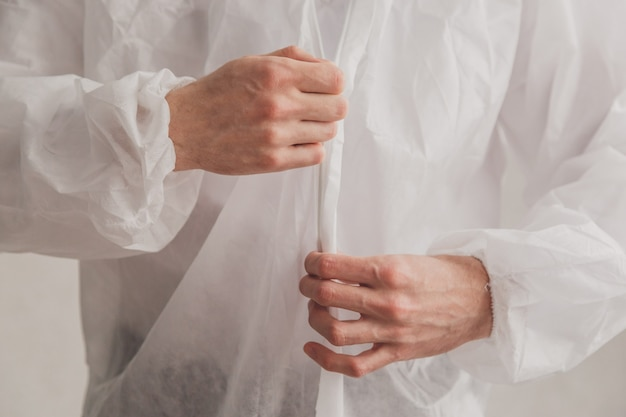 Doctor epidemiologist puts on white protective overalls, fastens a zipper, hands close-up