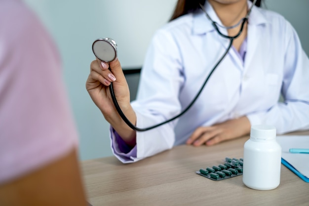 의사는 청진기로 환자를 평가하고 결과를 기록합니다.