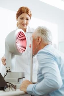 Врач каждый год. седовласый пожилой мужчина посещает окулиста в частной клинике на каждое ухо крупным планом