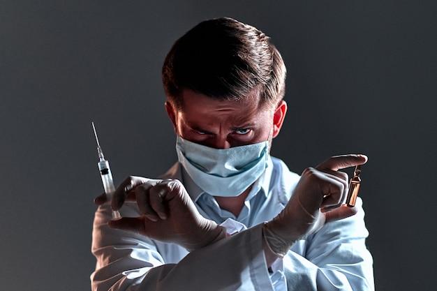 ドクターイーブル。白衣と医療用マスクを身に着けた若い男性医師は、腕を組んでアンプルと注射器を持ち、黒で隔離されています。