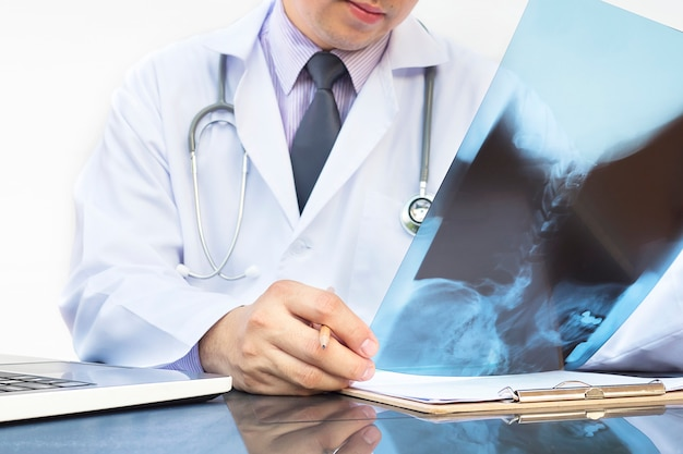Doctor examine x-ray film over white background