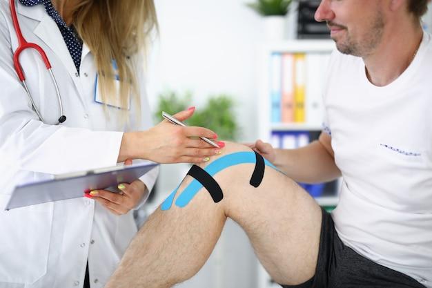 Врач осматривает у пациента травмированное колено с кинезиотейпом
