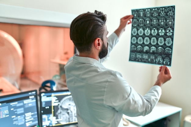 의사가 제어실에서 환자 뇌의 mri 스캔을 검사합니다.