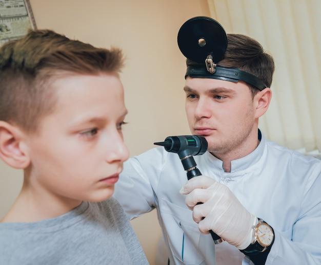 医師は耳鏡で少年の耳を調べます。