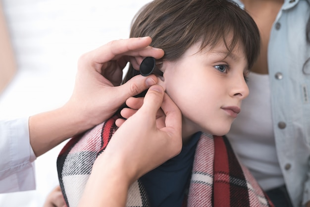 Doctor examines the ear of a sick boy.