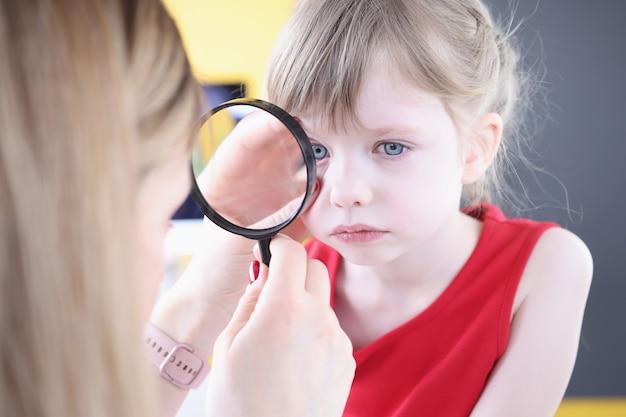 Врач осматривает глаз маленькой девочки через увеличительное стекло концепции детского конъюнктивита