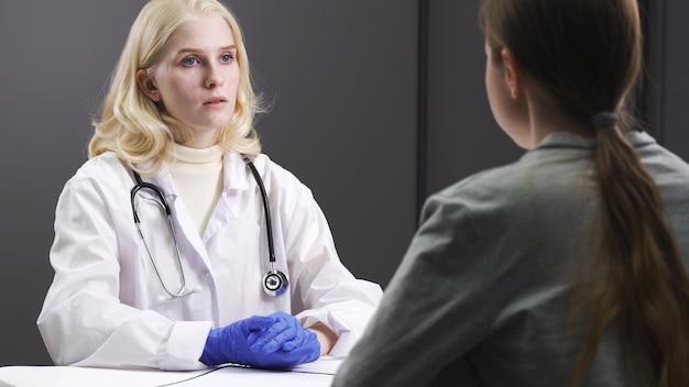 医師は医療記録を調べます。職場で白衣を着た女医