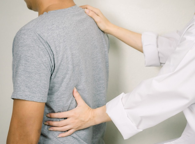 The doctor examines a patient with back pain inflammation of the back