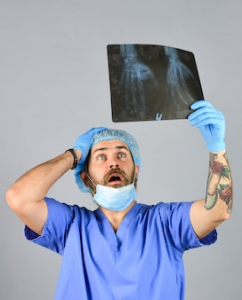 医師はレントゲン写真のスナップショットを調べます。外科医は損害賠償を見積もります。病院の緊急事態。ドクターユニフォーム。 x線の概念。 x線放射。医者は骨の写真を持っています。骨折と骨の損傷。