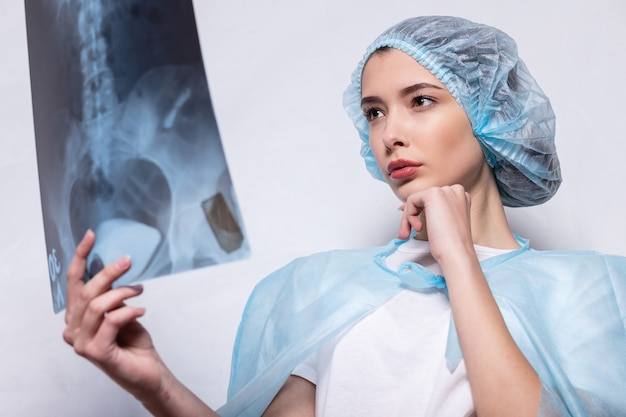 의사는 x- 선 사진을 검사합니다. 보호 마스크와 양복을 입은 여성이 손으로 안경을 들고 폐의 스냅 샷을 잡습니다.