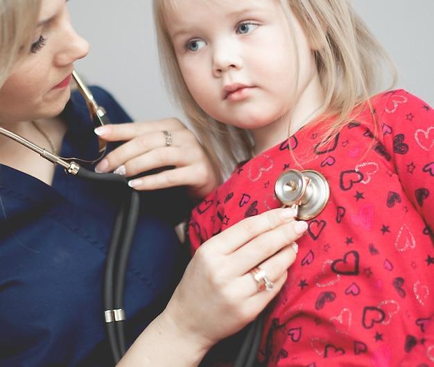 청진기에 의해 어린 소녀를 검사하는 의사