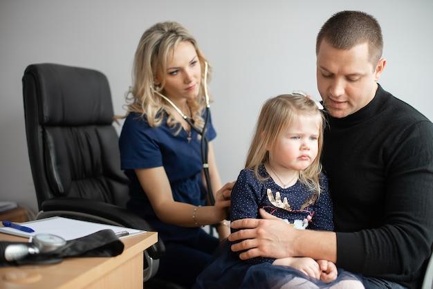 청진기로 어린 여자 아이를 검사하는 의사