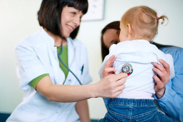 小さな女の子を調べる医者