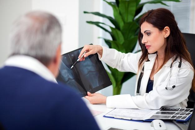 Доктор осматривает рентгенографию со своим пациентом