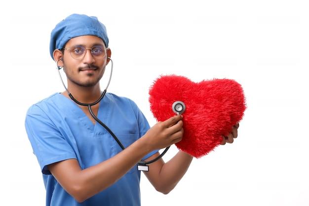 白い背景に対して聴診器で赤いハート型の枕を調べる医師。