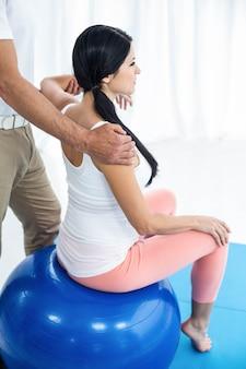 医師が検査し、妊娠中の女性に理学療法を与える