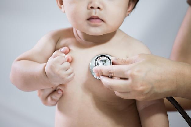 Доктор, изучающий азиатскую девочку и слушая ее сердце бить стетоскопом в больнице Premium Фотографии