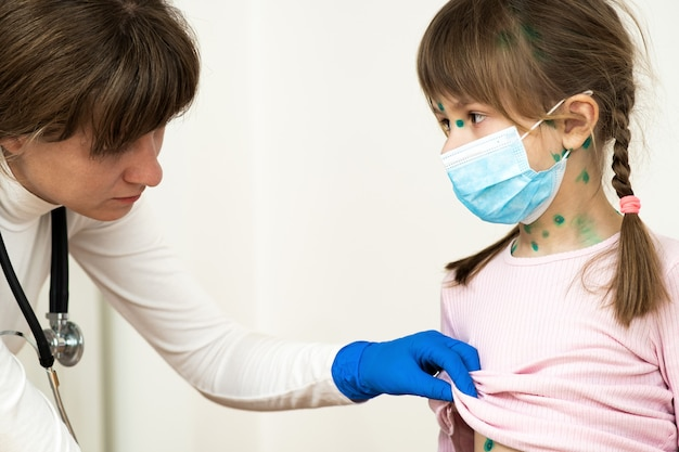 Doctor examining child girl covered with green rashes on face and stomach ill with chickenpox, measles or rubella virus.