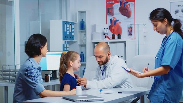 간호사가 부모와 이야기하는 동안 청진기를 사용하여 병원에서 아이를 검사하는 의사. 의료 서비스를 제공하는 내과 전문의 상담 진단 검사 치료