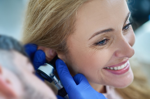 Doctor examining ear of smiling woman