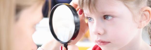 虫眼鏡を使用して少女の目を調べる医師。子供の概念における目の異物