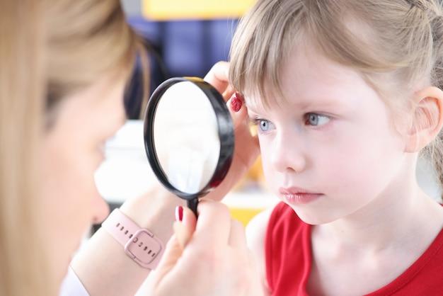 Доктор, исследующий глаз маленькой девочки с помощью увеличительного стекла